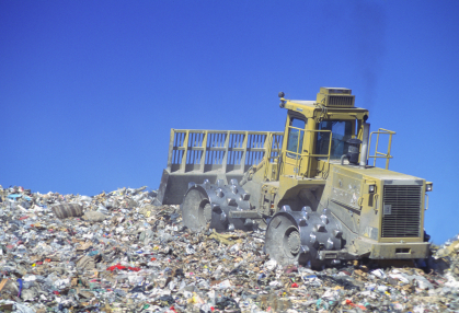 A piece of heavy machinery working on a landfill
